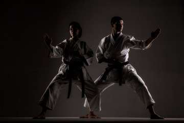 karate girl and boy posing against dark background