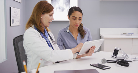 Charming female senior doctor using tablet computer to share lab results with young latina patient. Professional medical physician and patient looking at tablet portable device