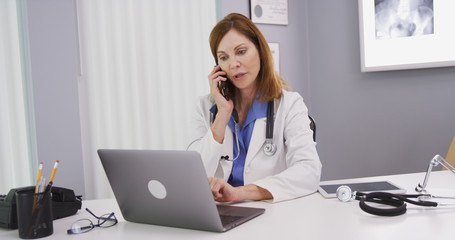 Attractive mid aged doctor using latop computer while talking on smartphone with colleague. Charming senior physician sitting in her office looking at notebook computer and chatting on cell phone