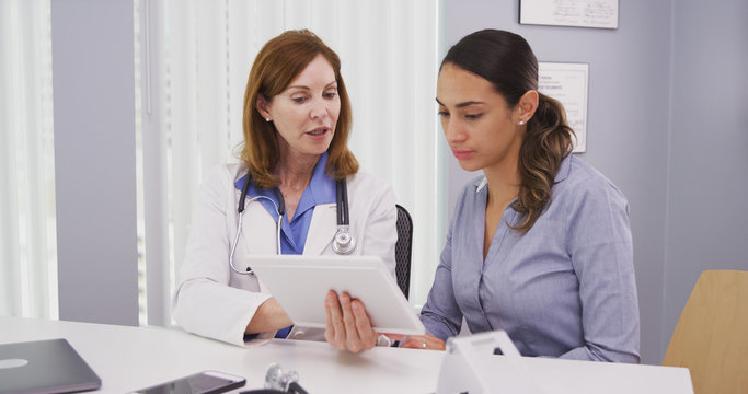 Portrait of beautiful latina patient consulting with doctor test results on portable tablet. Charming mid aged doctor reviewing medical results on high tech device with young patient