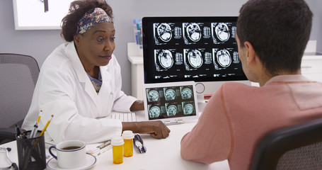 Portrait of senior African-American physician explaining to male patient effects of a concussion. Adult man visiting his doctor to review results from his brains ct-scans