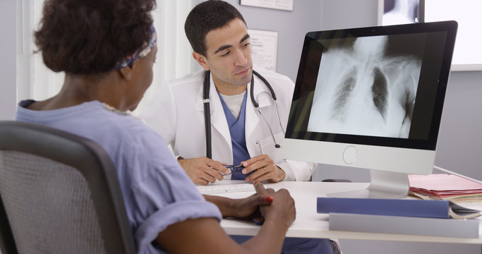 Old African patient paying doctor visit to review results from x-rays of lungs. Young Hispanic radiologist showing senior African woman an x ray of her lungs on computer