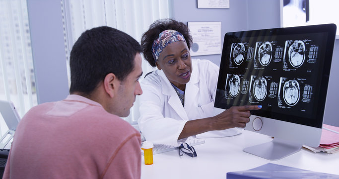 Close up of senior African doctor explaining to young patient his ct-scans of cranium. Intelligent female doctor using computer to show scans of patients brain