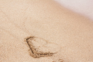 the heart painted on the sand is partially washed away by the wave