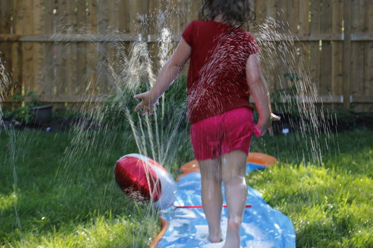 Happy girl slide to cool off on hot day during spring or summer