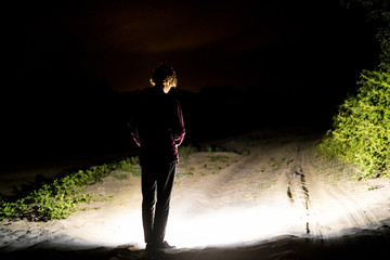 back view of man standing outdoor on night forest road lighting the way with electric flashlight d