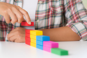 Concept of building success foundation. Women hand put colorful wooden blocks in the shape of a staircase