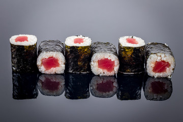 tuna roll on black background with reflection
