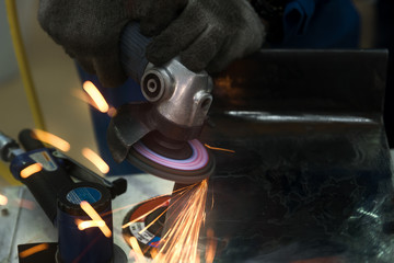 Worker using machine for coating and overlay steel for maintenance and repair in factory.