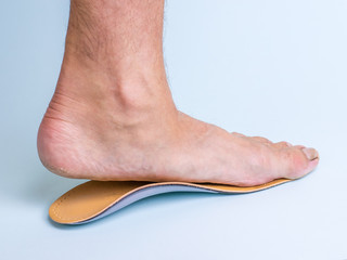 A man tries on an orthopedic insole on the left leg with signs of strong flat feet.