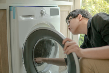 Young Asian technician looking into washing machine checking inside. Appliance maintenance in laundry at home. Technology concept