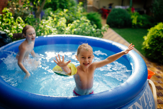Two cheerful cute little sisters playing and having fun, splashing and jumping in inflatable pool at backyard