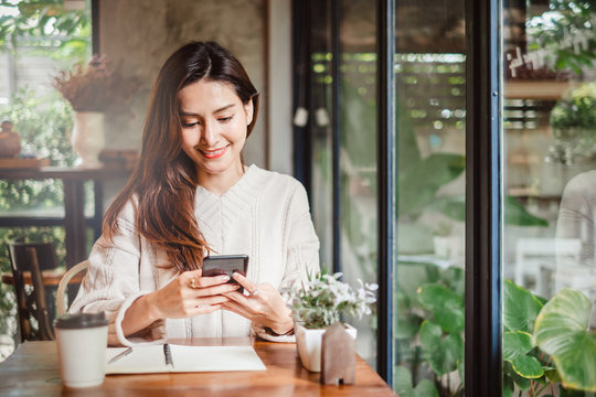 Young Asian beautiful woman using smart phone for business, online shopping, transfer money, financial, internet banking. in coffee shop cafe