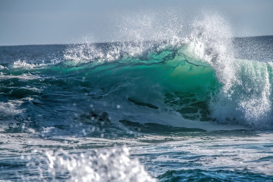 Turquoise blue wave breaking and spray