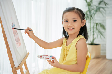 Portrait of smiling little Vietnamese girl enjoying painting on canvas