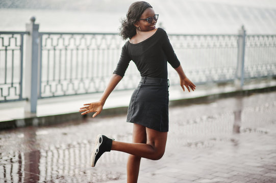 African american girl in sunglasses, black clothes and shirt posed outdoor. Fashionable black woman against rain of fountains.