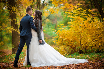 Groom and bride in autumn yellow leaves park. What to wear on the autumn wedding. Full length