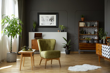 Green armchair standing in real photo of living room interior with retro cupboards, fresh plants, white rug and end table with tea set