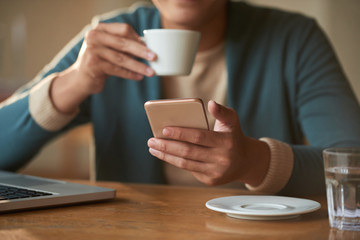 Smartphone in hands of young man drinking morning espresso