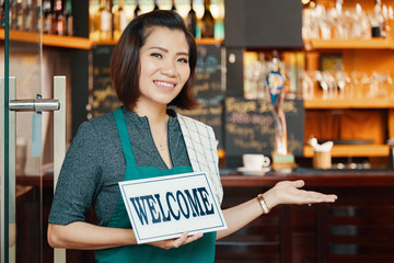 Portrait of smiling Vietnamese young woman inviting you to her bar