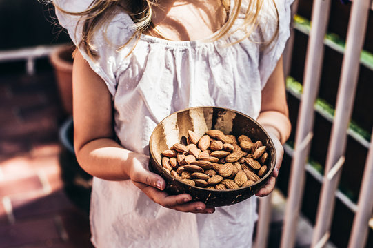 Cropped image of a girl holding a bowl full of almonds
