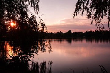 A beautiful sunset at a lake with orange color sky and silhouette trees