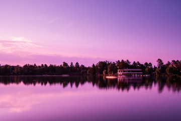 A beautiful sunset at a lake with purple sky, trees with reflection and a dock house