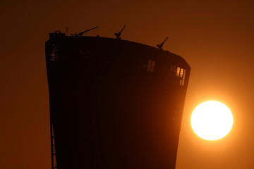 The sun can be seen rising behind a building in the financial district of central London
