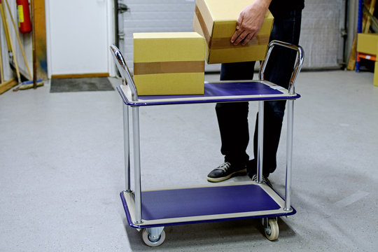 Man collects cardboard boxes to material handling trolley in warehouse