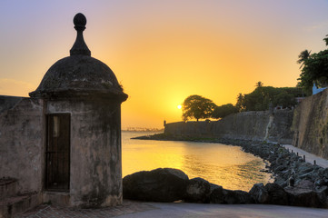 Poster Caraïben Beautiful summer sunset at the outer wall with sentry box of fort San Felipe del Morro in old San Juan in Puerto Rico