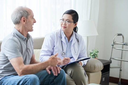 Asian adult woman with clipboard sitting on sofa in house of senior man during visit and listening to patient