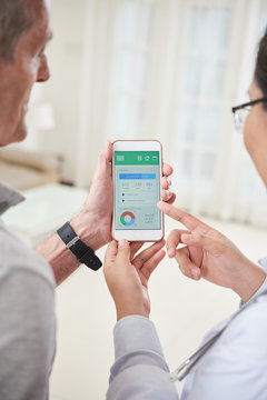 Crop doctor holding smartphone and showing application for healthy lifestyle during home visit