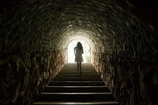 Girl walking throug dark tunnel into light