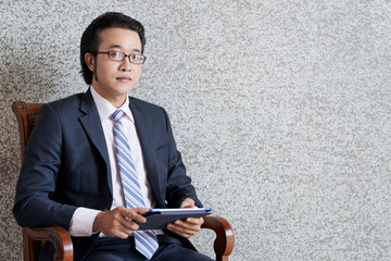 Elegant young Asian businessman in eyeglasses sitting in armchair with tablet in hands looking seriously at camera