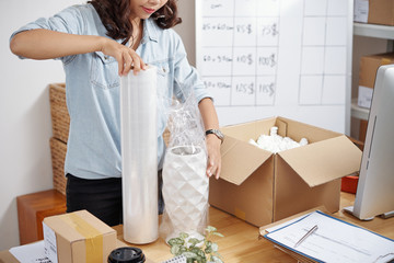 Young postwoman working with online order at her workplace, she packing vase in box