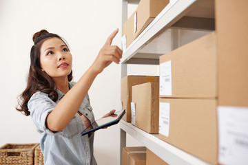 Young postwoman using tablet pc for work, she is looking for parcel on the shelves