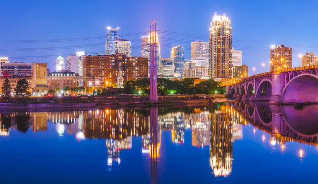 Minneapolis skyline with reflection in river at night.