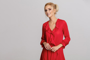 Beautiful smiling blond woman in red dress isolated on gray background