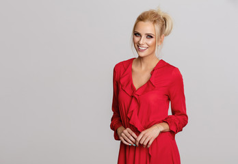 Beautiful smiling blond woman in red dress posing on gray background