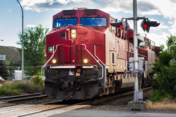 Powerful Diesel Locomotive Pulling a Cargo Train Moving Past a Level Crossing at Sunset