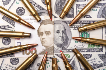 Ukrainian hryvnia, dollar, money close-up with military cartridges. Banknotes The concept of economy and financing of war.
