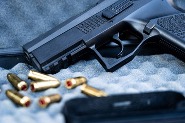 Close up view of bullets and handgun. Shallow depth of field. Focus on a pistol.