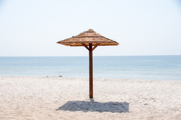 view on beautiful range of bamboo parasols isolated on beach of praia de quarteira in blue sky,...