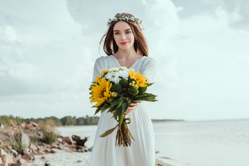 attractive girl holding bouquet with sunflowers on sea shore