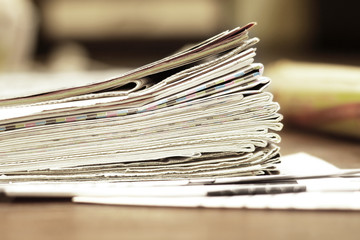 Pile of newspapers. Folded and stacked pages with news, headlines, articles and photos on the wooden table. Daily papers in the morning. Selective focus, blurred background