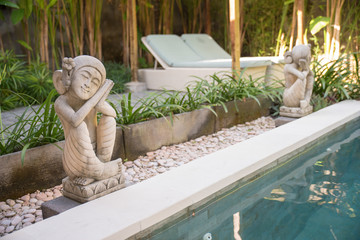 relaxing statue beside pool beds in Bali