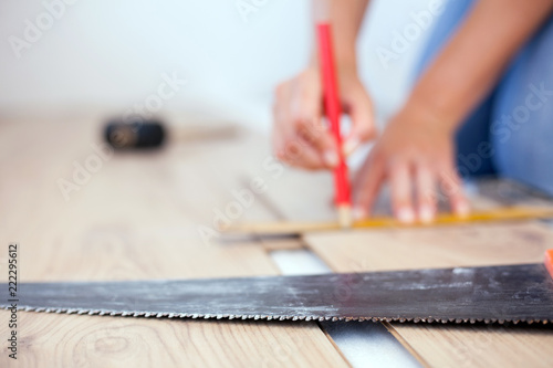 Selective Focus Photo Of A Hand Saw In Foreground Woman Measuring