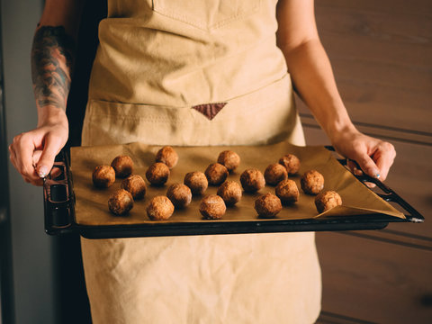 Raw frozen meat balls on baking sheet with paper