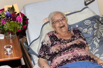 Alte Frau hat zum Geburtstag Besuch mit Hund im Seniorenheim oder Altenheim und ist fröhlich gut gelaunt