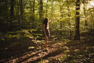 Young brunette with a dress and long hair relaxing in the middle of the forest in a sunset of summer